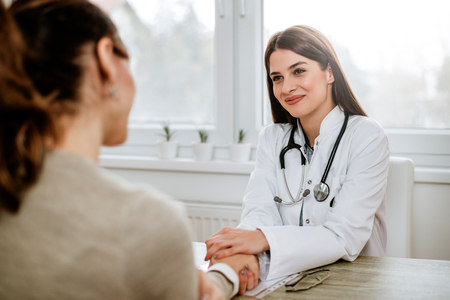 Friendly female doctor holding female patient's hand for encouragement and empathy. 写真素材