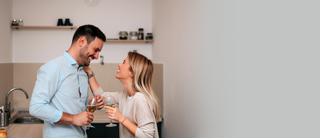Attractive couple in kitchen talking and smiling. Imagens
