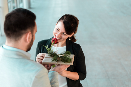 Beautiful smiling young woman receiving rose and gift from her boyfriend.