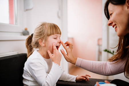 Little girl and mother applying face creme. Skincare concept.