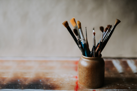 Photo of clean paint brushes in a ceramic jar.