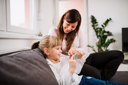 Smiling little girl and her mother using smartphone.