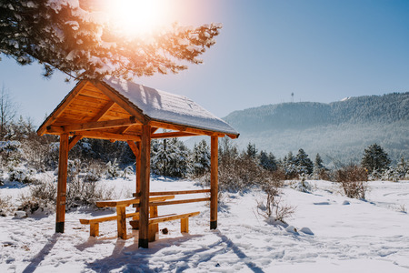 Table and benches on the snow covered mountain with a beautiful view. Sunny day.
