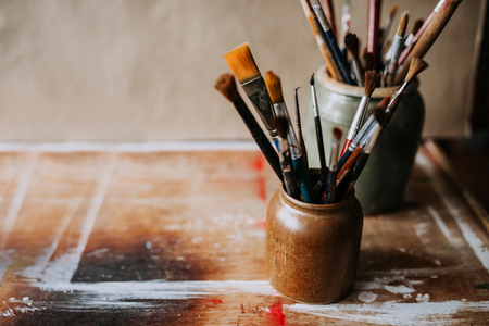 Artistic image of paint brushes in a ceramic jar.