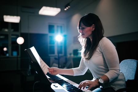 Inspired pianist reading a sheet music while playing synthesizer piano.