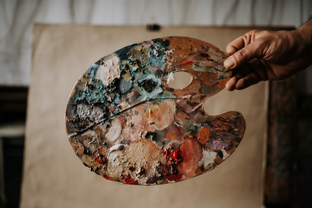 Artists hand holding palette. 스톡 콘텐츠