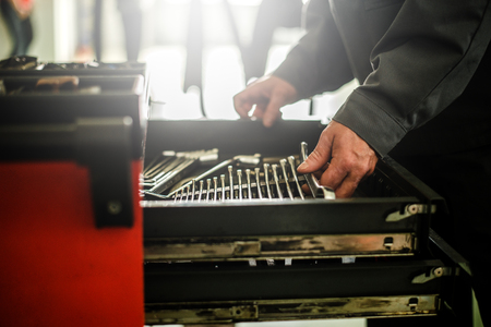 Mechanic standing at drawer with tools. Banque d'images