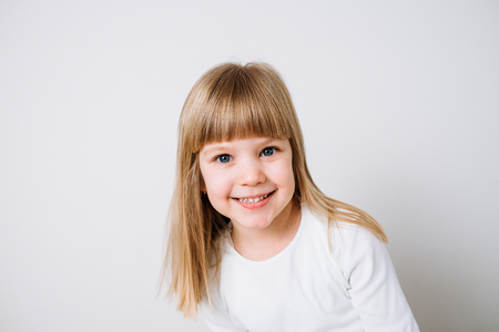Portrait of a blonde little girl on white background.