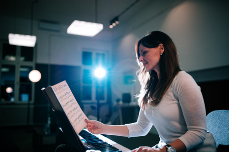 Side view of female pianist playing while turning sheet music.
