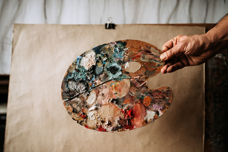 Image of a painters hand with palette.