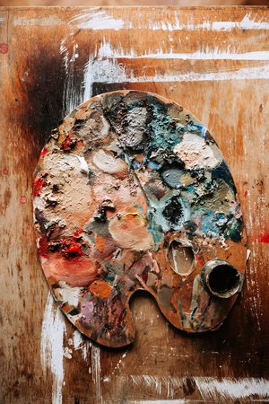 Painters palette on wooden background.