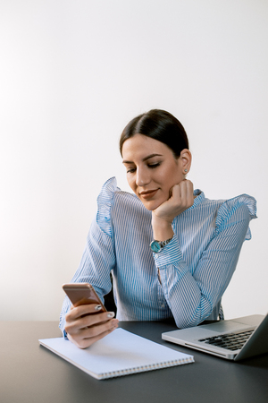 Charming woman using smartphone at office desk. Banque d'images