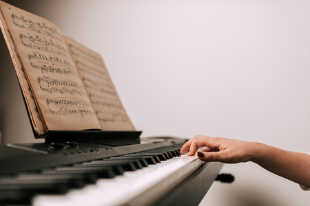 Playing piano from a classical sheet music. Close-up.