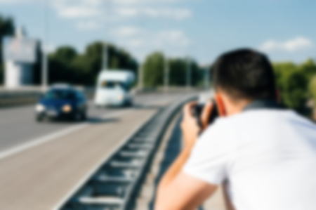 Blurry image of young photographer while taking photo on the road.