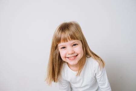 Smiling little girl dressed in white on isolated background.