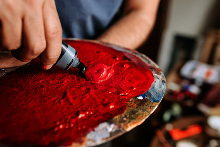 Artist squeeze red paint from the tube on the palette.