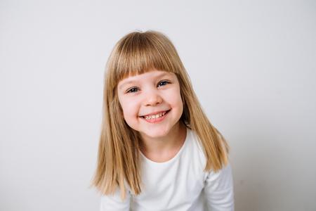 Joyful little girl on isolated background. Close-up
