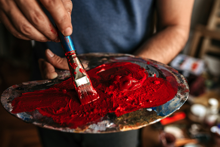 Artist holding palette with red color. Close-up