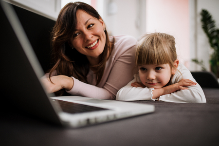 Smiling young mother and daughter watching cartoon on laptop, lying on a sofa.