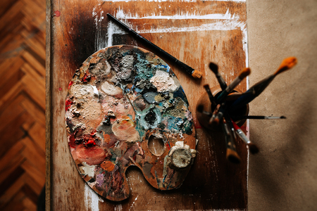 Top view of artist's palette and brushes on a wooden background.