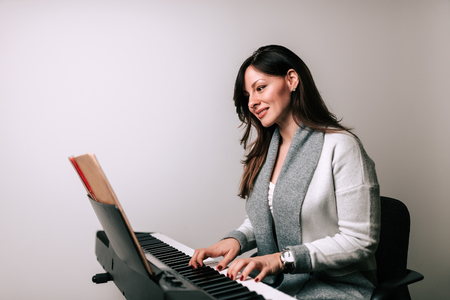 Beautiful woman playing synthesizer from music sheet. Isolated background.
