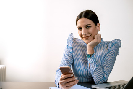 Woman in a blue shirt using phone while sitting at desk. Looking at camera.