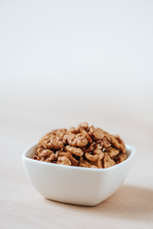 Walnut kernels in a bowl on table. Vertical shot of Walnuts.