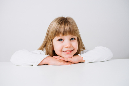 Close-up image of a smiling little girl leaning with arms crossed on white background.