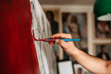 Painting red. Artist working on artwork. Banque d'images