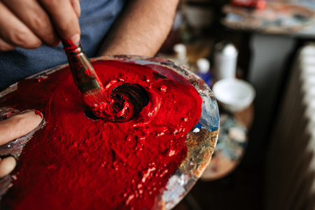 Close-up image of artist hand mixing red and blue color on the palette.
