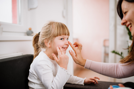 Smiling mother applying creme on her little daughter face.