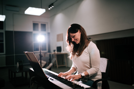 Female composer playing synthesizer piano Stock fotó
