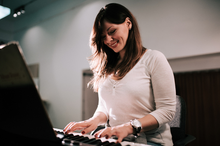 Charming young woman playing synthesizer piano.