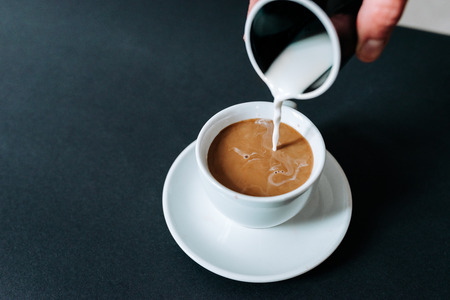Close-up of milk being poured into the cup of coffee on dark background.