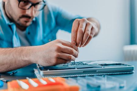 Ingenieur repareert laptop met schroevendraaier. Close-up.