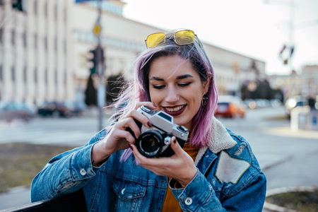 Gorgeous urban girl photographer sitting at city street, using camera.