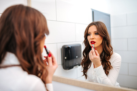 Portrait on mirror of a beautiful girl applying red lipstick on her lips.  Stock Photo
