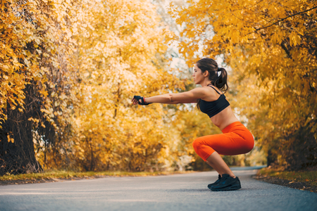 Beautiful woman working out in autumn park.
