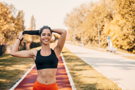 Woman tying hair in ponytail getting ready for run.