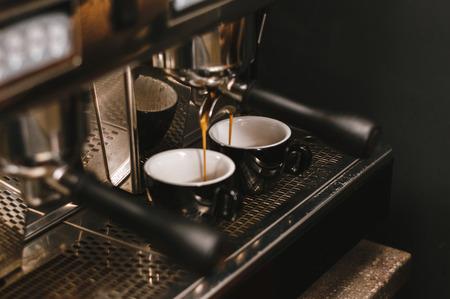 Professional espresso machine pouring fresh coffee into a ceramic cup. Stock Photo