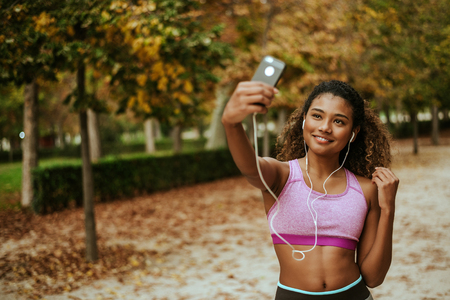 Young sporty hispanic woman taking selfie outside. Stock Photo