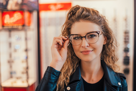 View of a young attractive woman trying glasses at the optician. Stock Photo