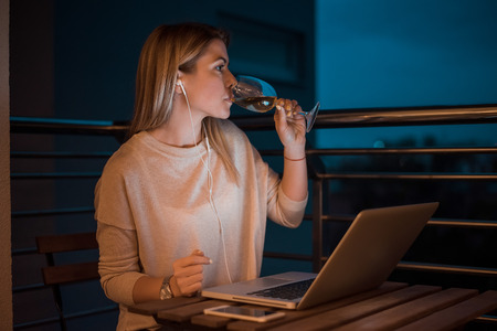 Beautiful young woman drinking wine while working on laptop at night. High ISO image. Stock Photo - 98407651