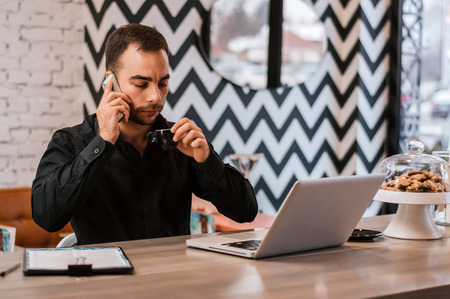 Busy businessman making a call and having a coffee while working from city cafe Stock Photo
