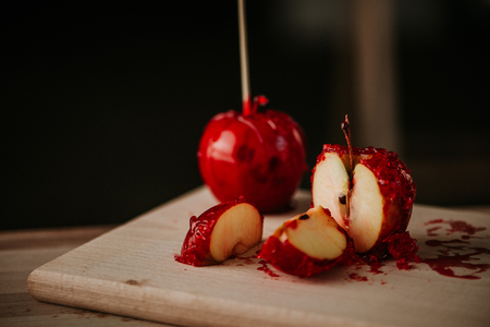 Sliced candy apples on wooden board. Stock Photo