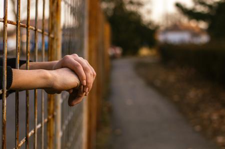 Prisoner's arms resting in prison jail yard Stock Photo - 98255890