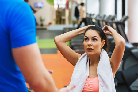 Young male personal fitness trainer talks to his female client and giving her advices for motivation.