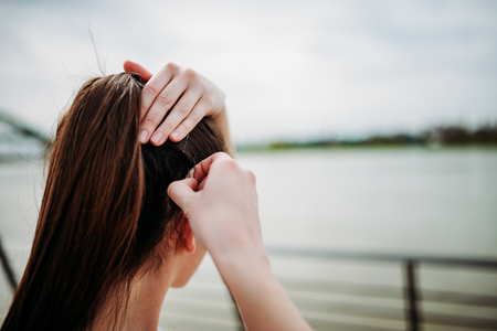 Girl putting bobby pins in hair outdoors. Close-up. Banque d'images