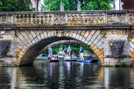 CAMBRIDGE, UK - JULY 11, 2014 : Professional punter in busy River Cam under the  oldest bridge, Claire bridge, with visitors  on the boats.
