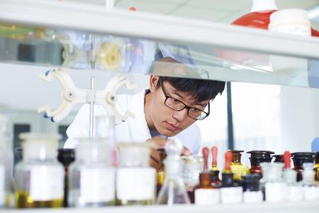 1 つの男性中国研究所科学者が試験管のラボで働いて